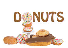 Donuts sign display using a doughnut as part of word. Variety of Donuts isolated on white background with word DONUTS above pile, using a sprinkle donut for the Stock Photography