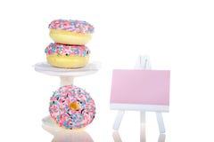 Donuts som staplas på sockel och isoleras med den rosa staffli royaltyfri bild