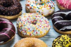 Donuts som täckas med isläggning, choklad, muttrar med olikt arkivbilder