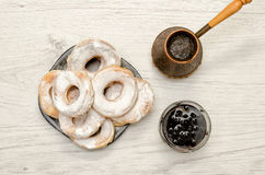 Donuts sprinkled with powdered sugar, fresh coffee and jam on a light wooden fone. Top view Stock Photos