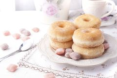 Donuts with sugar on a plate on a light background. Calorie Sweets for breakfast. Free place . Top view. stock photo