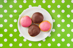 Donuts with sweet topping on a plate, top view royalty free stock image