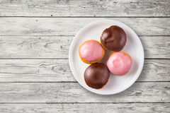 Donuts with sweet topping on a plate, top view. Top view of homemade tasty donuts with sweet strawberry topping and chocolate topping on a plate over rustic Royalty Free Stock Photo