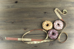 Donuts and tape measure on wooden background Stock Images