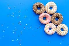 Donuts verfraaide suikerglazuur en bestrooit op blauw achtergrond hoogste meningsexemplaar ruimteruimte voor tekst royalty-vrije stock fotografie