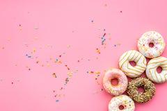 Donuts verfraaide suikerglazuur en bestrooit op roze achtergrond hoogste meningsexemplaar ruimtepatroon stock afbeeldingen