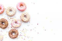 Donuts verfraaide suikerglazuur en bestrooit op wit achtergrond hoogste meningsexemplaar ruimtepatroon royalty-vrije stock afbeelding