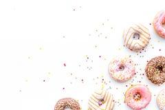 Donuts verfraaide suikerglazuur en bestrooit op wit achtergrond hoogste meningsexemplaar ruimtepatroon royalty-vrije stock afbeeldingen