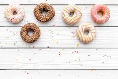 Donuts verfraaide suikerglazuur en bestrooit op wit achtergrond hoogste meningsexemplaar ruimteruimte voor tekst stock afbeelding