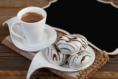 Donuts with white chocolate and cup of coffee on wooden background with black writing board. Horizontal shot Royalty Free Stock Image