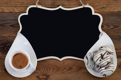 Donuts with white chocolate and cup of coffee on wooden background with black writing board. Horizontal shot Stock Photography