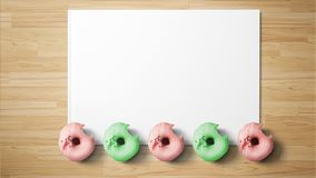 Donuts on white paper on wooden background royalty free stock photo