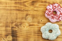 Donuts on wooden background. Sweet donuts with sugar icing. Unhealthy food. The dangers of obesity. Stock Photos