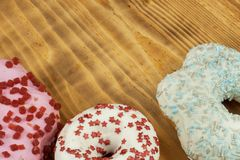 Donuts on wooden background. Sweet donuts with sugar icing. Unhealthy food. The dangers of obesity. Royalty Free Stock Photos