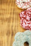 Donuts on wooden background. Sweet donuts with sugar icing. Unhealthy food. The dangers of obesity. Stock Image