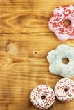 Donuts on wooden background. Sweet donuts with sugar icing. Unhealthy food. The dangers of obesity. Royalty Free Stock Photography