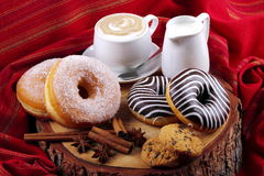 Donuts zebra and sugary donuts. Donut with chocolate and sugar on wooden stump with cinnamon and background with red cloth Royalty Free Stock Image