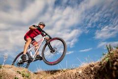 Donwhill del montar a caballo del ciclista de la montaña contra el cielo azul de la tarde foto de archivo libre de regalías