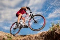 Donwhill del montar a caballo del ciclista de la montaña contra el cielo azul de la tarde imagenes de archivo