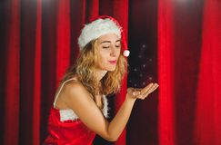 Donzela atrativa da neve em um vestido e em um chapéu vermelhos em um fundo do curtainsr vermelho imagens de stock royalty free