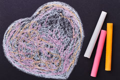 Doodle heart on black background. Colorful chalk sticks and heart. Simple but creative surprise Stock Image