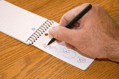 Doodle Small. A hand doodles on a note pad. All drawings created by the photographer Stock Image