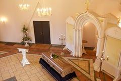 Doodskist met bloemen en tribune bij begrafenis in kerk stock foto