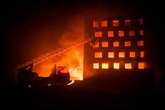 Doof de brand van een privé huis bij nacht Stuk speelgoed brandvrachtwagen met de lange ladder en het branden bouw bij nacht Bran stock afbeeldingen