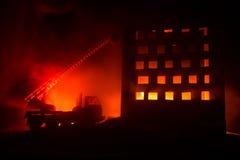 Doof de brand van een privé huis bij nacht Stuk speelgoed brandvrachtwagen met de lange ladder en het branden bouw bij nacht Bran royalty-vrije stock afbeelding