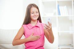Doof meisje die gebruikend gebarentaal op de nok van smartphone spreken stock foto