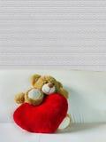 Dool mignon d'ours avec le grand coeur rouge sur le sofa blanc et l'espace vide Photos stock