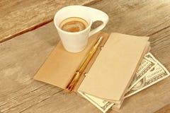 打开葡萄酒笔记薄,金笔,一百doolar和杯Espre 免版税库存图片