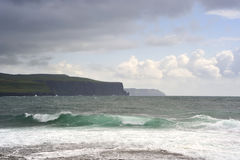 Doolin Bay. Waves rush to shore in Doolin Bay, during summer storm,with Cliffs Of Moher visible on horizon royalty free stock photos