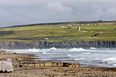 Doolin beach with Doonagore Castle, county Clare, Ireland. Doolin beach with a small village and Doonagore Castle in the background, waves crashing Stock Images