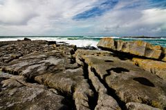 Doolin's Bay, The Burren. Panorama. Doolin's Bay, The Burren, County Clare, Ireland. Cliff's of Moher in the distance. A Ferry Boat is sailing to Aran Islands Royalty Free Stock Photography