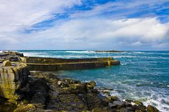 Doolin's Bay, The Burren. Panorama. Doolin's Bay, The Burren, County Clare, Ireland. Cliff's of Moher in the distance. A Ferry Boat is sailing to Aran Islands Royalty Free Stock Images