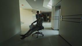 Dooly tiró de dos hombres de negocios locos que montaban la silla de la oficina y que lanzaban los papeles para arriba mientras q