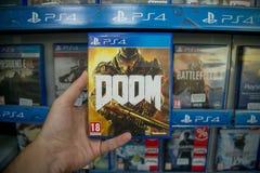 Doom. Bratislava, Slovakia, circa april 2017: Man holding Doom videogame on Sony Playstation 4 console in store Royalty Free Stock Photos