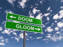 Doom and gloom. Text 'doom and gloom' in uppercase white letters on two green highway style sign boards with arrows pointing in opposite directions, blue sky and Stock Photography