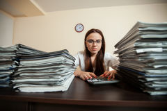Doomed accountant against big stacks of documents. Doomed female accountant against big stacks of documents and calculator Stock Images