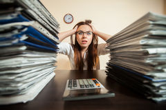 Doomed accountant against big stacks of documents. Doomed female accountant against big stacks of documents and calculator Royalty Free Stock Photography