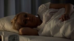 Doomed and hopeless woman in depression lying in her bed at nursing home, aging royalty free stock photo