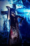 Doomsday. Bloodthirsty zombi with a knife standing at the night cemetery in the mist and moonlight Stock Images