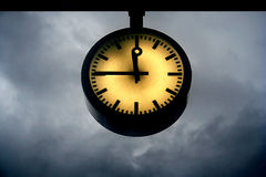 Doomsday Clock. Clock at a quarter to twelve with a background of dark rainclouds stock photography