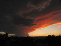 Doomsday like cloud formation over the city. Weird but powerful cloud formation over the city with sun light at dusk Royalty Free Stock Images