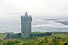 Doonagore Castle with Doolin bay in the background, west of Ireland. Doonagore Castle at dusk, near Doolin bay, west of Ireland royalty free stock photos