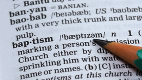 Doopsel, potlood die woord in woordenboek, christelijke godsdiensttak, geloof richten stock footage