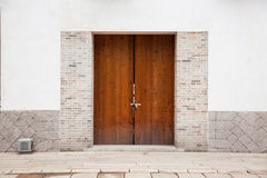 Door. Closed door and white stone wall Royalty Free Stock Photography