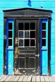 Door. Old black wood door with windows and turqoise walls Stock Photos