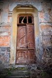The door of an abandoned house. Overgrown with dry branches Royalty Free Stock Photo